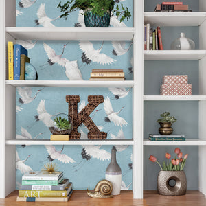 Halcyon Peel & Stick Wallpaper he hand-painted cranes look picturesque flying over a marbled blue background.  Hung on back of shelves.
