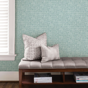 Aqua Poplin Texture peel and stick wallpaper- light blue wallpaper hung on wall in sitting area.