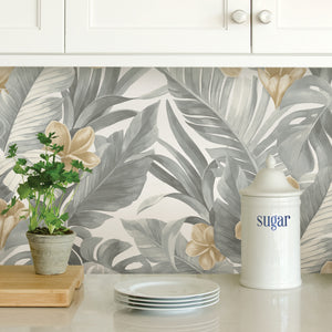 Neutral Paradise Peel & Stick Wallpaper-Palm fronds, banana leaves, and flowers are given a neutral spin in grey and tan. gives it a tropical flare. Used as backsplash under kitchen cabinet