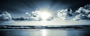 Tranquility Panoramic Wall Mural-blue shades depict a morning ocean with a glistening sun rising from behind the clouds.