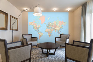 Worldwide Wall Mural-A bright blue background makes the oceans. The pastel countries are labeled with main cities. hung in living room
