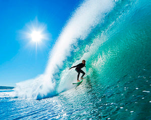 ohpopsi Adrenalin Wall Mural-cresting wave curves over a surfer under clear blue sky.