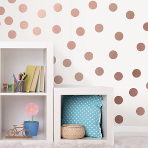 Metallic Rose Gold Dots Wall Art Kit-peel and stick rose gold dots which is a modern pink.  Shown on child's wall.
