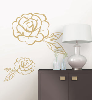 Stay Rose Wall Art Kit-2 different sized peel and stick roses that are golden in color and have an outlined design.  Hung by cabinet.
