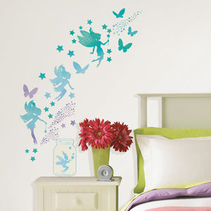 Fairy Dust Glow in the Dark Wall Art Kit -peel and stick wall paper pixie dust, these green and blue glow in the dark fairy decals also includes stars and butterflies.  Shown on wall during day.