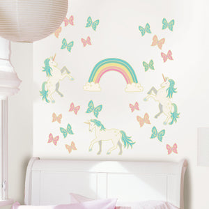Enchanting Unicorns Glow in the Dark Wall Art Kit -peel and stick wallpaper that glows in the dark unicorns, butterflies and rainbow beautiful shades of green, orange and pink pastels.  Shown on wall during the day.