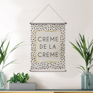 Creme De La Creme Wall Tapestry has black speckled design and gold accents hung on wall in front room.