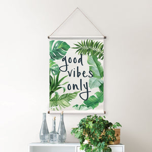 Good Vibes Wall Tapestry Palm has fronds and banana leaves that frame  good vibes only quote which is written in black.  Hung on wall