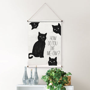 Like Me Meow Wall Tapestry features four curious black cats and a comical pun, How Do You Like Me-Ow, printed in black.  Hung on wall over table.