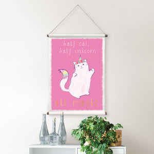 Half Cat Tapestry-Quote- Half cat, half unicorn, all magic, is written in white and gold with a floral crown and rainbow tail and horn.  Hung on wall over chest