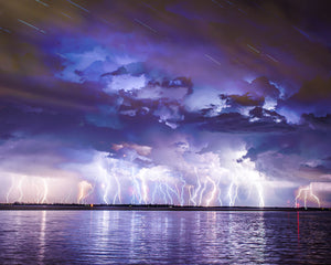 Lightning Strikes Wall Mural-A storm above water is captured in an array of blues and purples.