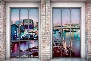 Loft Wall Mural-night scene places you in the center of a colorful metropolis filled with flashing lights and stoic skyscrapers. shown through 2  brick framed windows.