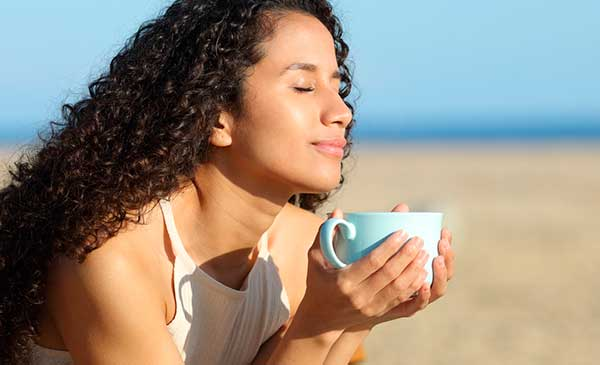 girl relieving anxiety by sipping tea on beach