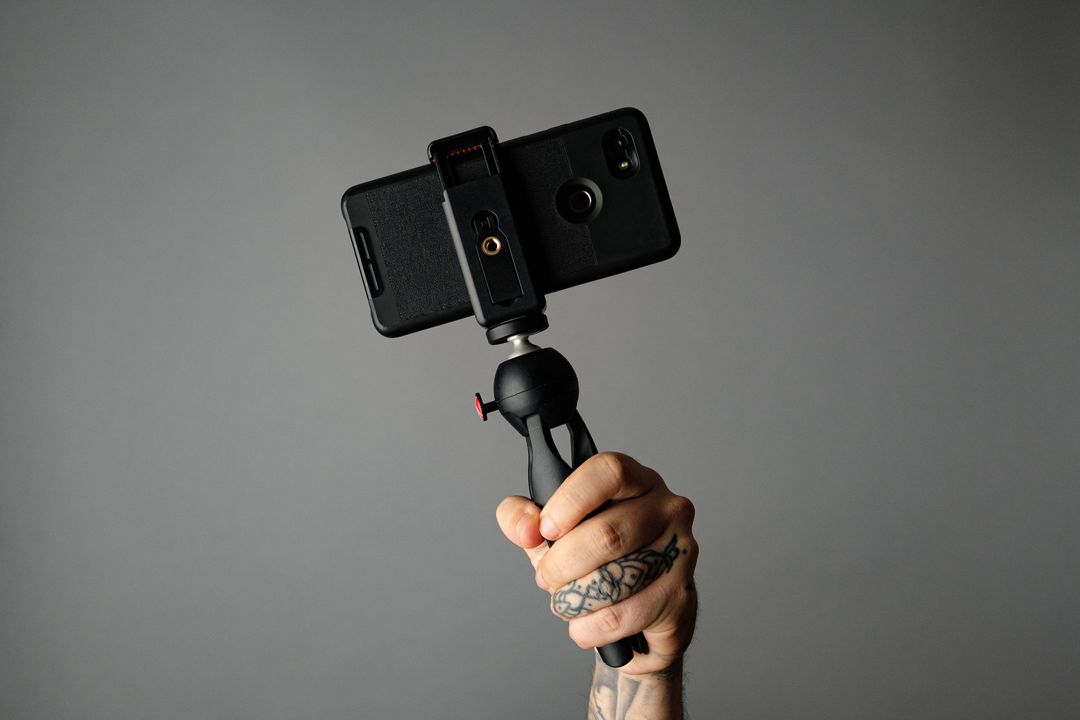 Hand Holding Mobile Phone And Tripod