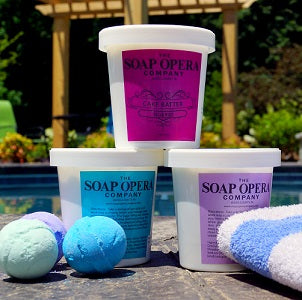 Containers of sugar whip and bath bombs by a pool
