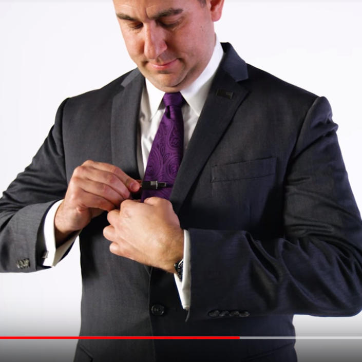 Man in suit putting American Flag tie-clip on