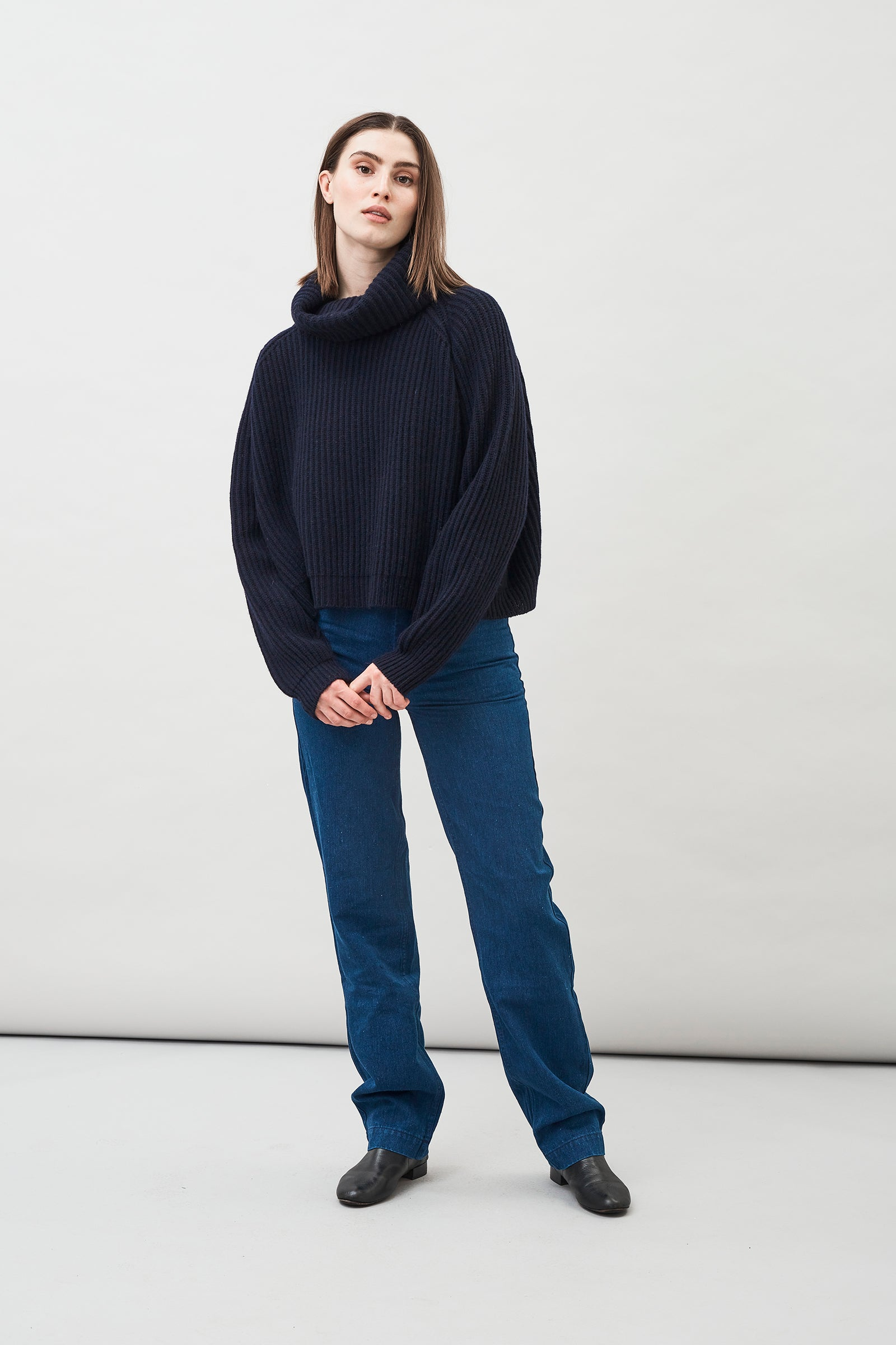 Della Wool Roll Neck Ribbed Sweater in Navy Blue with a cropped silhouette and fold-down collar.