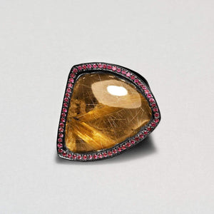 Large rutile quartz framed with small pink rubies. Soft triangular shape.