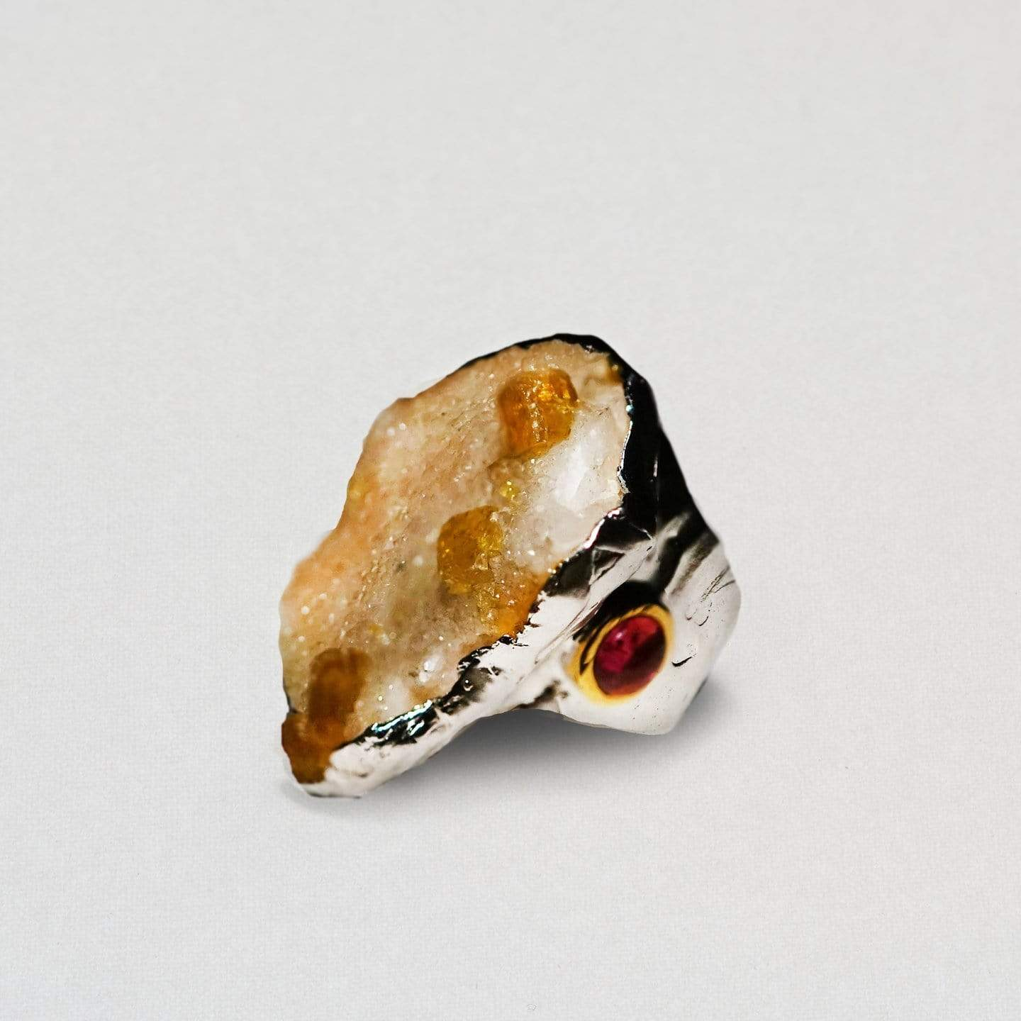 A rounded flat surface on the top of a white rhodium ring. Within the rounded section is a matrix tourmaline. It varies from pale white to deep orange and is richly textured.