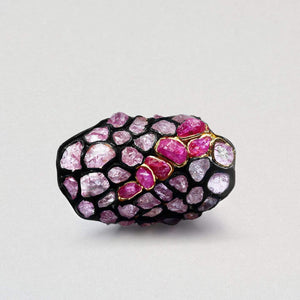 A large oval shaped black anthracite ring. It has pink rubies embedded in the surface. There are many of them, all different rounded shapes. A central section is slightly deeper pink and is trimmed in gold.