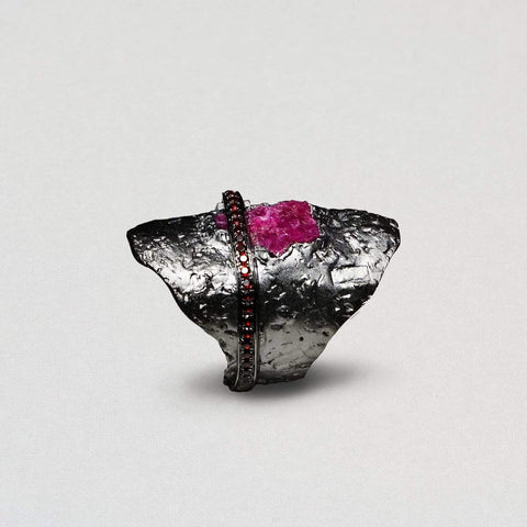 A large ring with a texutred surface made of black rhodium. It has a large ruby at the centre with rough edges. A line of garnets slices across the middle.