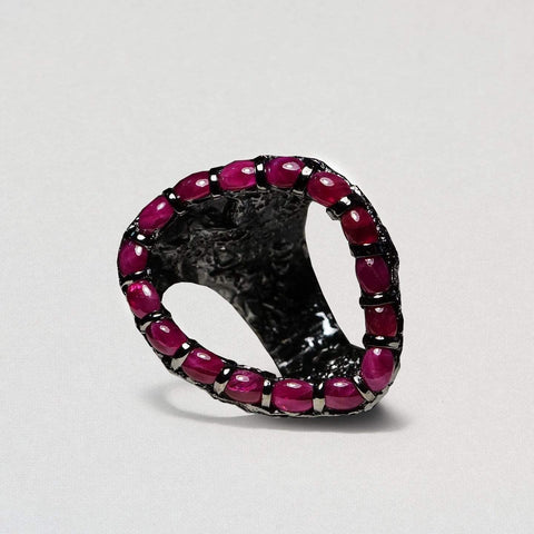A wide open rounded line of rubies with an open hole at the centre. Black rhodium edges each gemstone.
