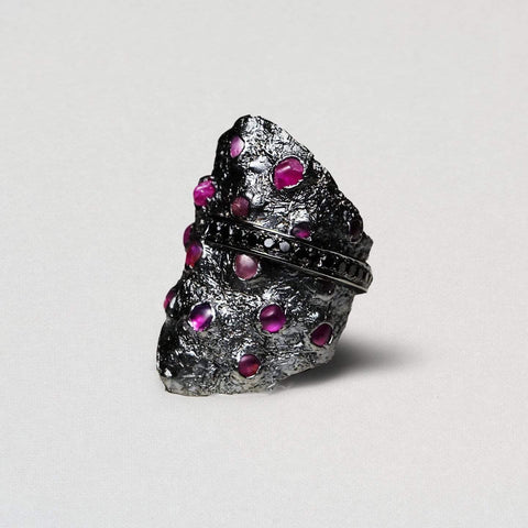 A large textured ring dotted with pink rubies across its surface. A line of black spinels cuts through the centre.