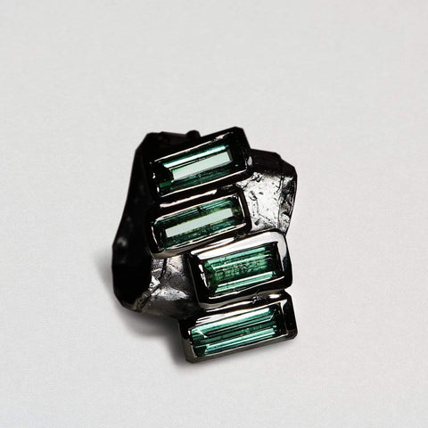 A square shaped black rhodium ring very dark in color. Four green tourmalines sit in a diagonal line, spiling off the edge. They are a very dark green.