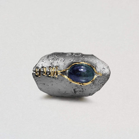 A black rhodium oval-like ring has a large blue sapphire near the top. Below is a rip-like groove banded together with gold lines to look like stitches.