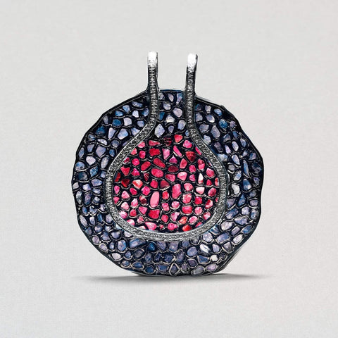 A rounded shaped pendant has two circular sections, one within the other. The outer ring is encrusted with blue sapphires. The inner circle has many rubies.A line of white sapphires creates a slim border between them.