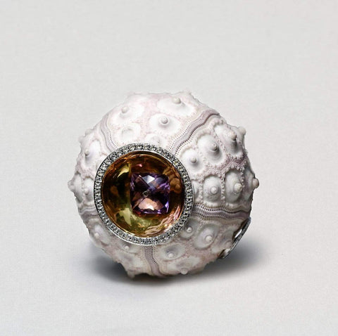 A bright white sea shell that looks like a sea urchin has been hollowed out and trimmed round its open gaps with white sapphires. At the front is a large round amethyst with a deep purple color.