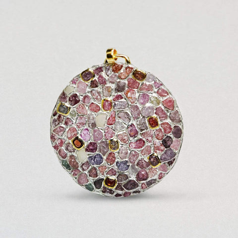 A large flat circular pendant is encrusted with white sapphires and rough rubies. It has a gold clasp at the top. The rubies are various shades of pink, red and orange.