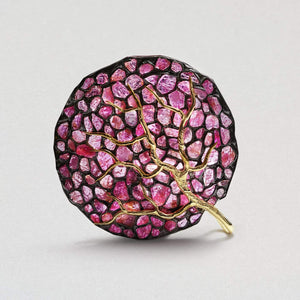 A large pendant in a circular shape of black anthracite. Many rubies are encrusted on the surface in a range of pale to deep pink colors. A tree-like shape of gold lines curves down towards the centre.