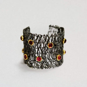 A barrel shaped bangle in black rhodium. It is made of lots of wire-like lines of precious metal criss crossing. There are pink and orange tourmaline gemstones trimmed in gold, dotted across the surface.