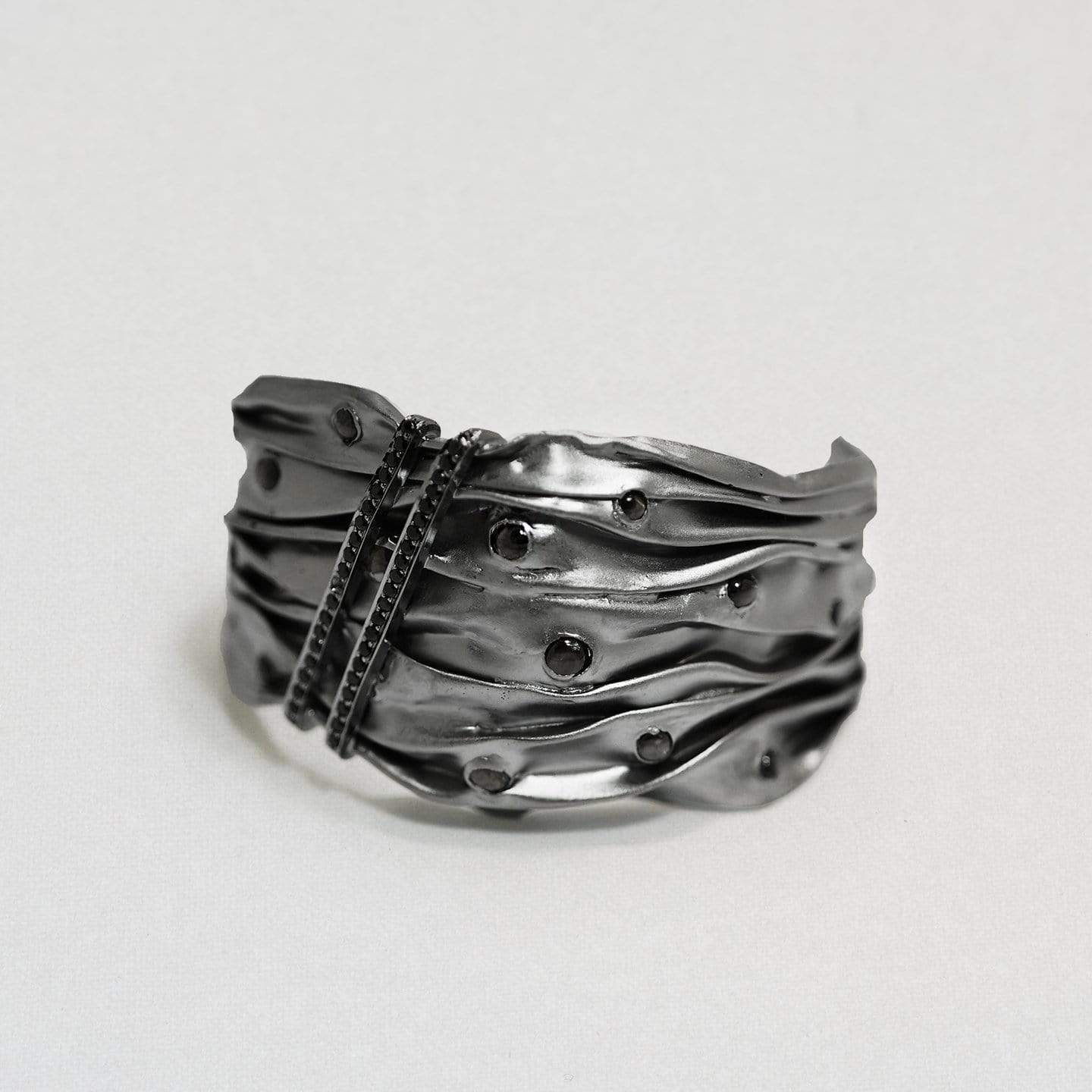 A rippled style texture on a black rhodium bangle. Within the ripples are rounded smoky quartz gemstones. Two diagonal lines of black spinel gemstones slice up on one side diagonally.