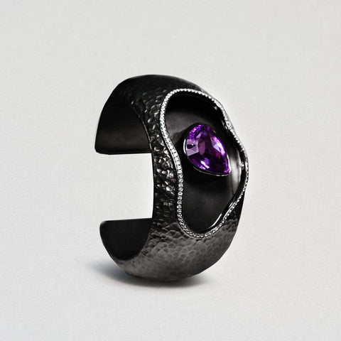 A dark black rhodium bangle with a pitted surface. A wavy opening at the top that curves around a central amethyst. It is a teardrop shape and very deep purple. A trim of white topaz goes around the opening.