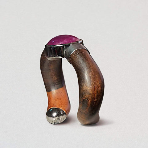 A black rhodium bangle in a very unusual shape. Brackets of metal hold onto arms of the bangle that look like dark smooth tree brances. At the centre of the join is a round ruby in a deep pink-purple color.