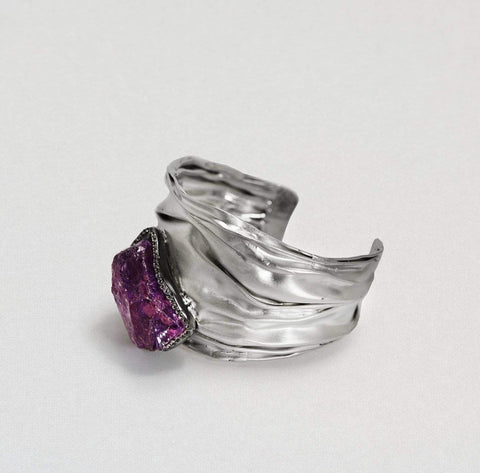 A black rhodium bangle with a wavy pleated look. At the bottom is a large raw amethyst that stands out from the bangle. It is trimmed in white topaz gemstones.