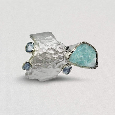 A barrel style ring that has a pitted texture. It has a large aquamarine gemstone that hangs off one end. Three smaller aquamarine gemstones are on the eges.