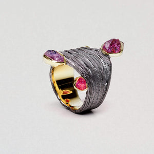 A barrel ring is wavy in shape and has a criss cross of metal lines. Several rubies of unusual shape hang off the edges and are trimmed with gold.