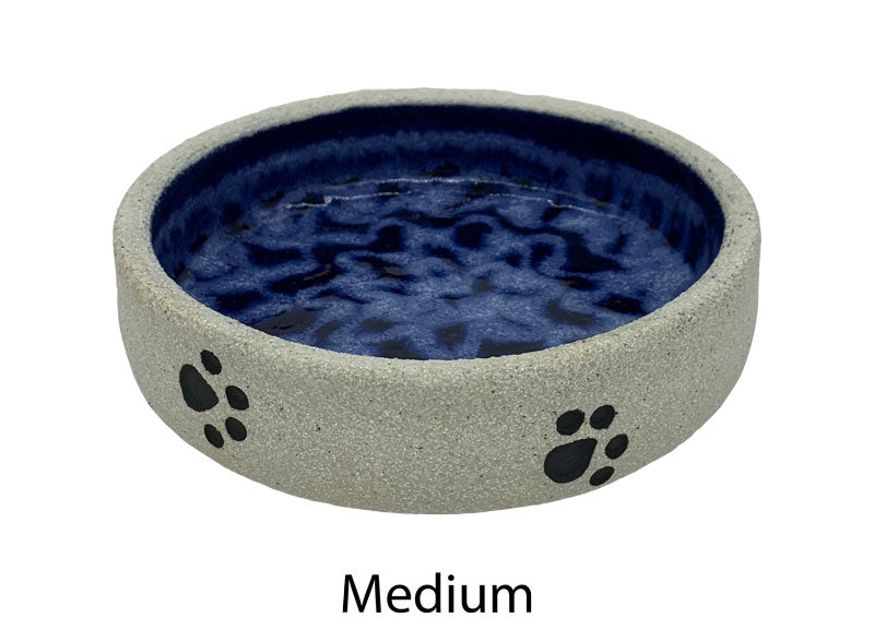 Amazing dog bowl with paw prints on outside edge the whole way around and blue glazing inside. Stone wear is very strong. Medium size showing from above