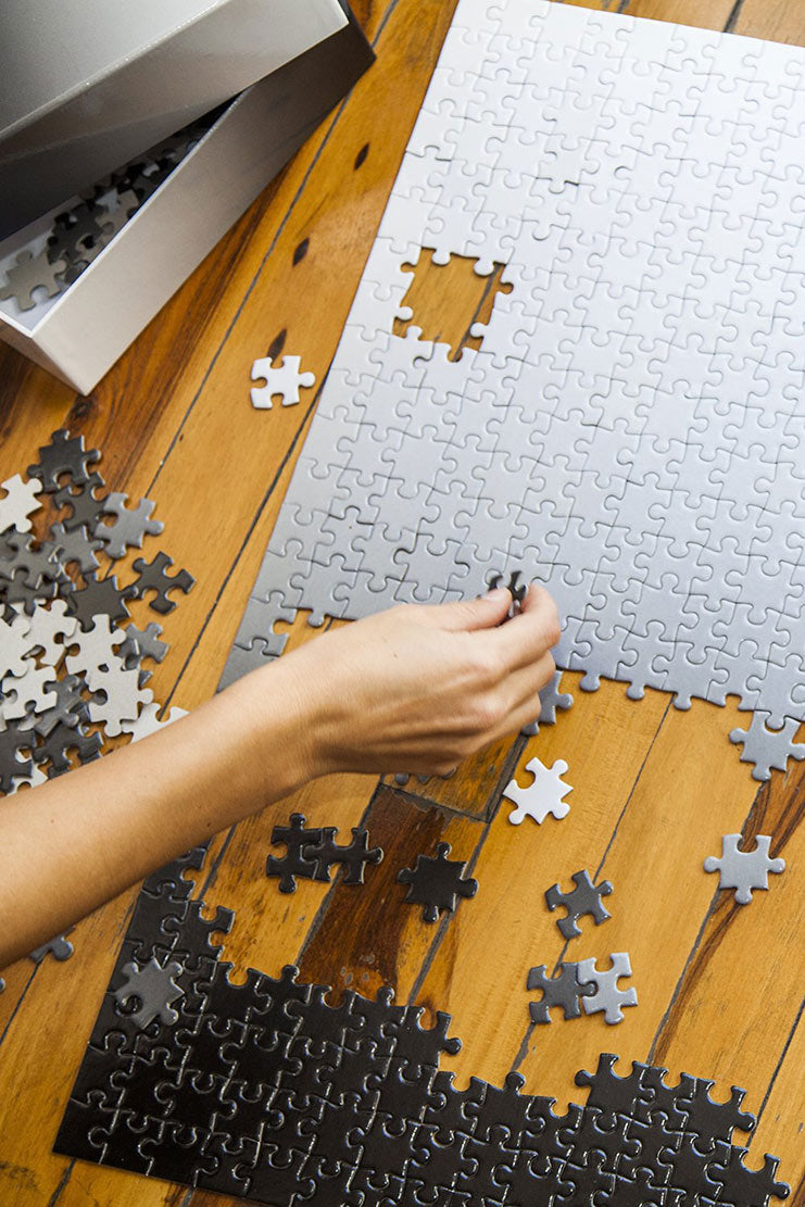 person putting black gradient puzzle together