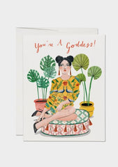 "woman in dress sitting on cushion in front of potted plants with words ""you're a goddess"""
