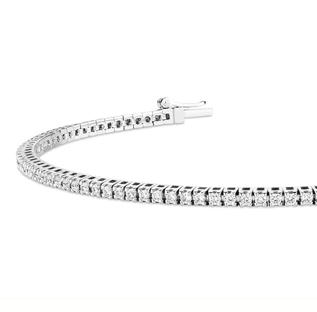 Close up of a white gold diamond bracelet on a plain white background.