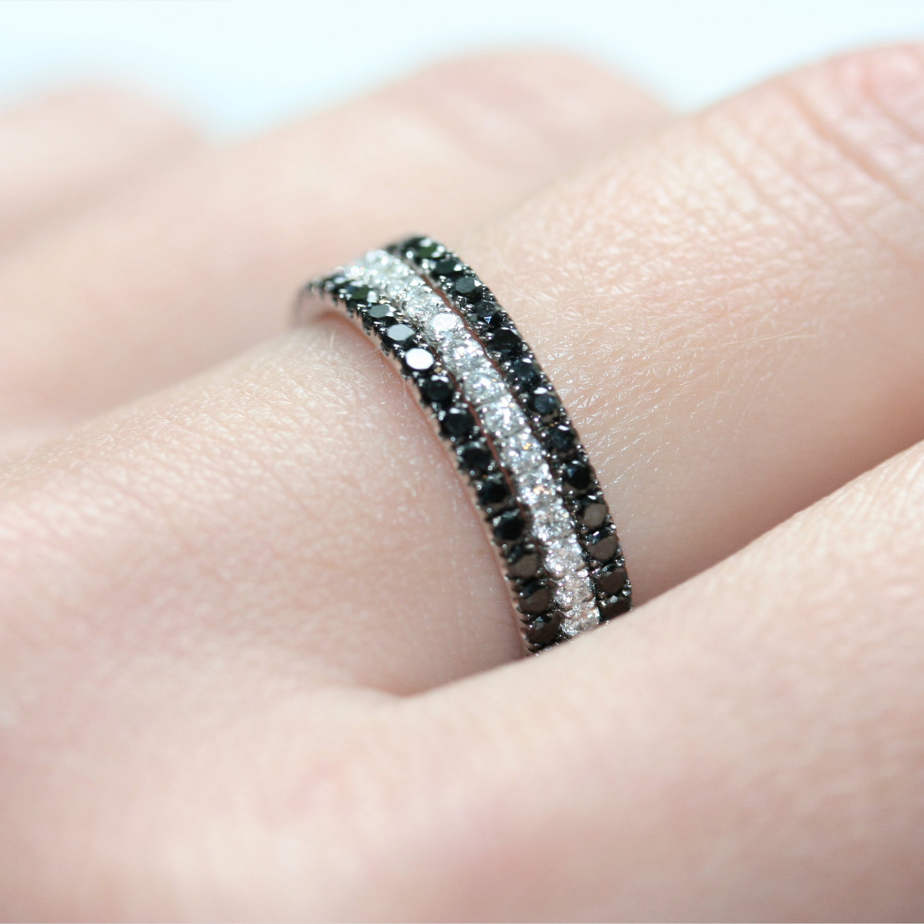 Closeup of a black diamond ring with 18 carat white gold on a lady's hand, as part of a set