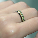 Green garnet ring in 18ct white gold on a hand stacked next to other eternity rings.