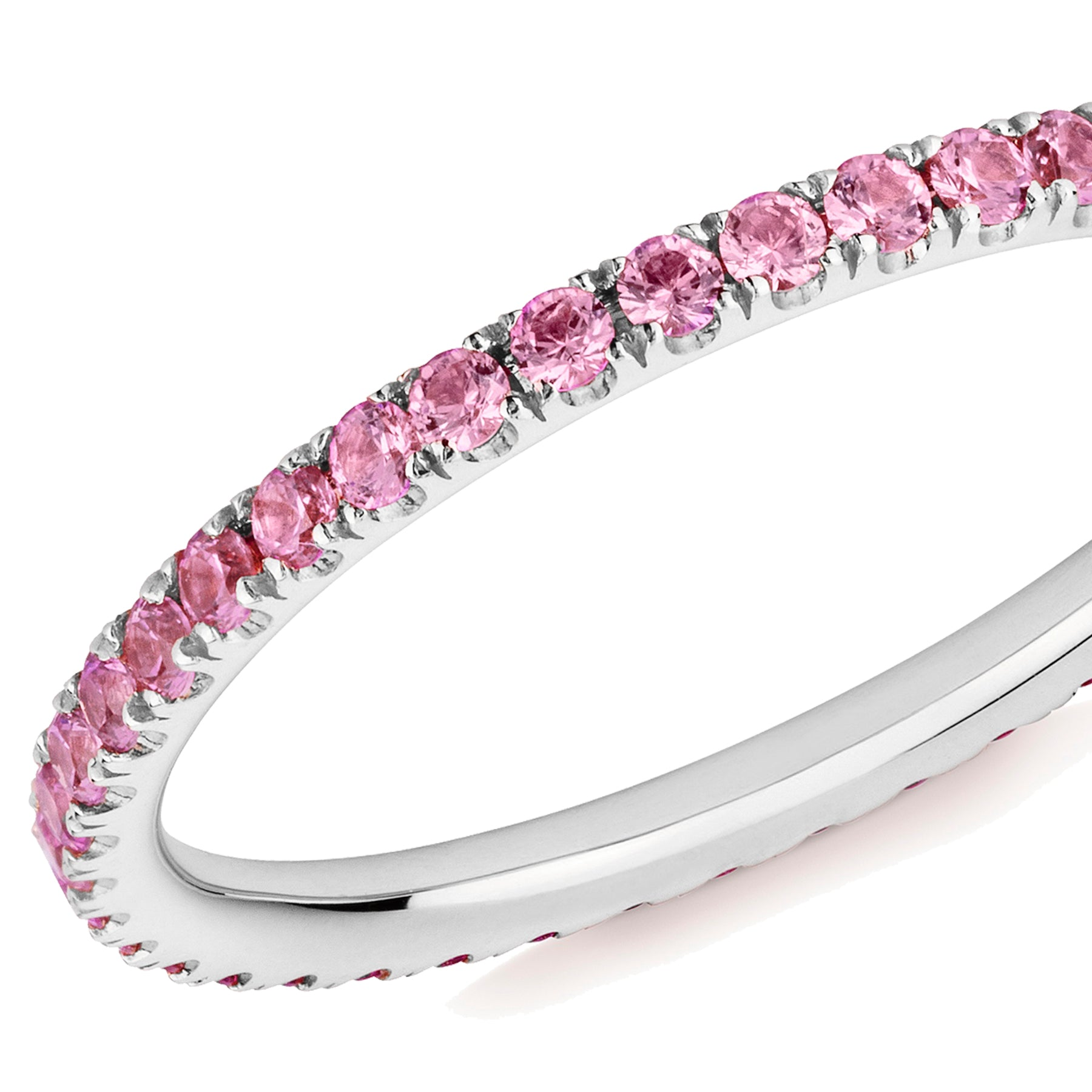 Closeup of a pink sapphire eternity ring in platinum on a white background.