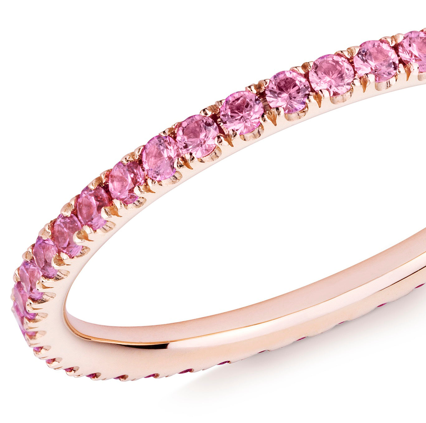Closeup of a pink sapphire eternity ring in 18ct rose gold on a white background.