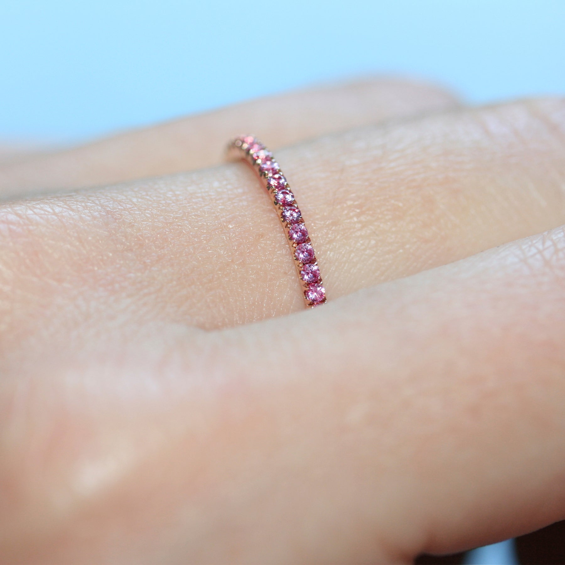 Closeup of a pink sapphire eternity ring in 18ct rose gold on a hand