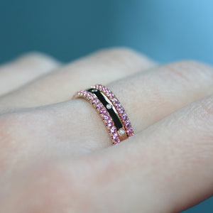 Pink sapphire eternity ring in platinum on a hand alongside other eternity rings